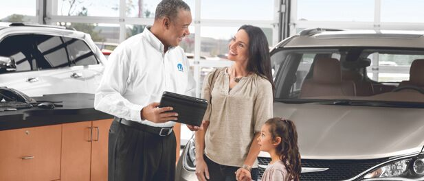 Mopar agent in dealership showroom checks FCA recall information for a mother with her child